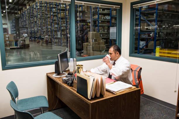 Employé installé à son bureau dans un atelier industriel