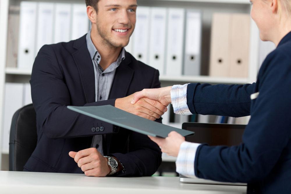 deux personnes se serrent la main, une tient un dossier dans l'autre main