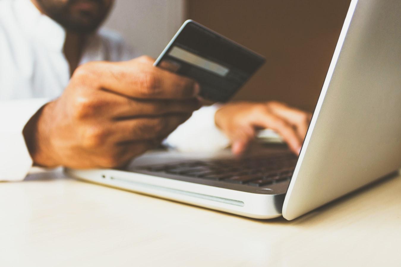 Jeune homme qui passe une commande avec sa carte bleue sur un site e-commerce