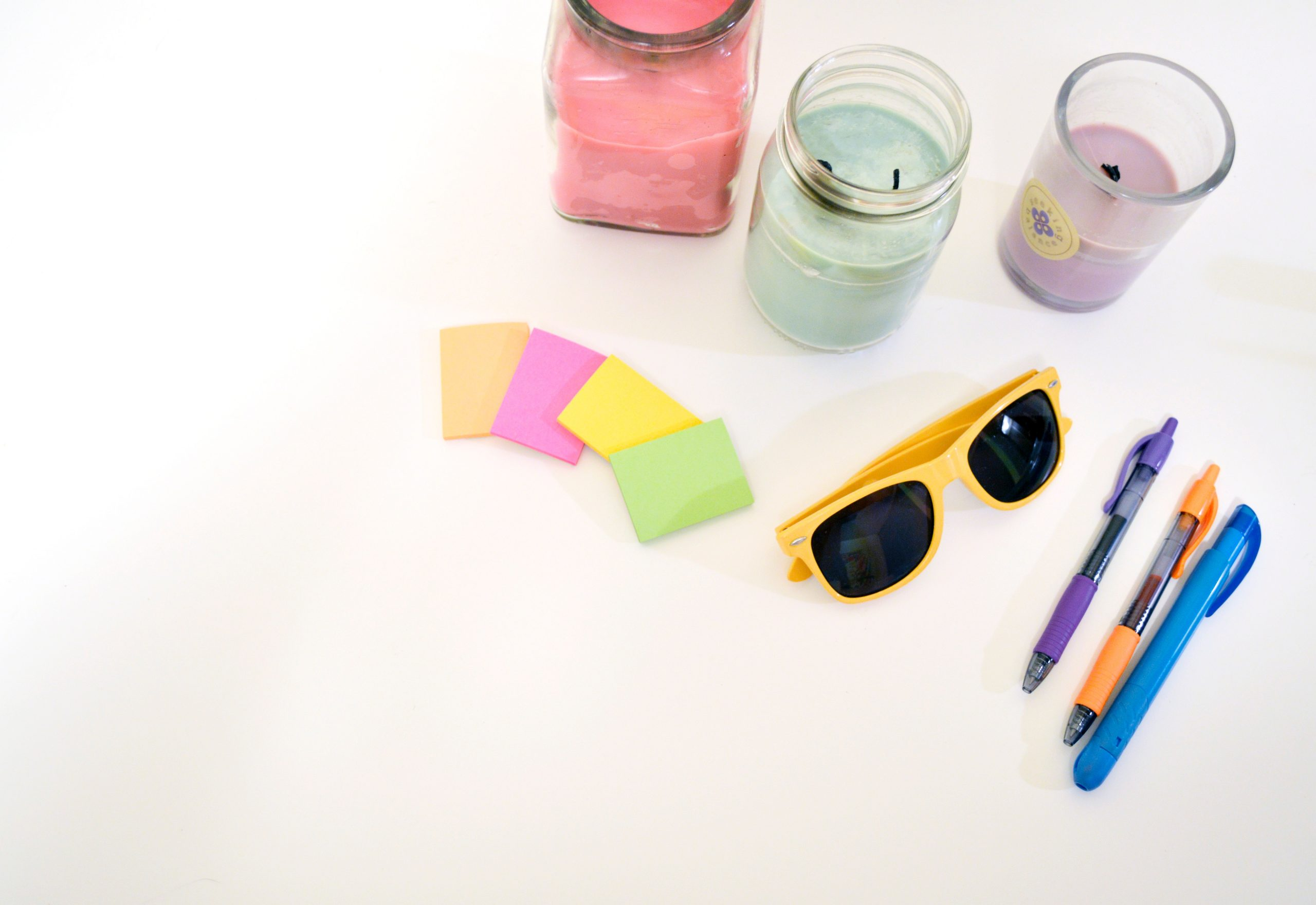 goodies sur fond blanc lunettes de soleil post it bougies stylos